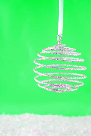 hanging sparkly swirly  christmas ball with reflection on green  surrounded by fake snow Stock Photo - 3815357