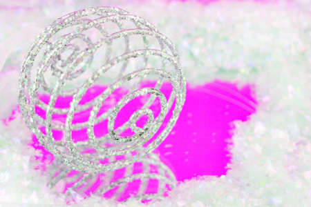 sparkly swirly  christmas ball with reflection on pink surrounded by fake snow