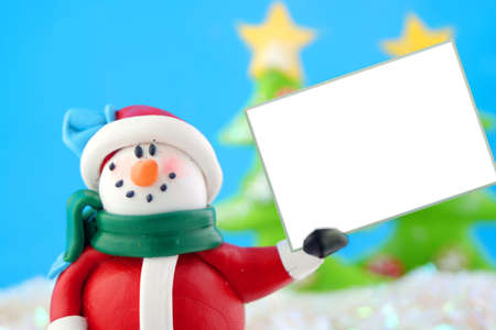 snowbank: fantasy wonderland scene with  snowman holding a blank white sign with christmas trees in the background Stock Photo