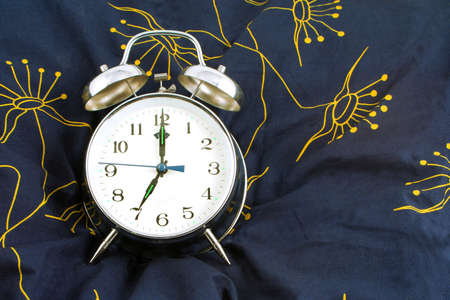 seven o'clock: alarm clock resting on a pillow showing 7 oclock, time to wake up