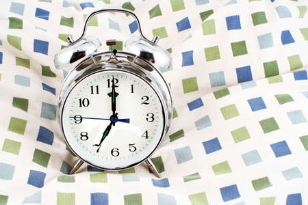 oclock: alarm clock resting on a pillow showing 7 oclock, time to wake up