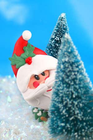 winter scene in glitter, Santa Claus is playing hide and go seek, peeking or hiding  behind miniature pine trees photo