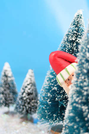 winter scene in glitter, Santa Claus is playing hide and go seek, peeking or hiding  behind miniature pine trees