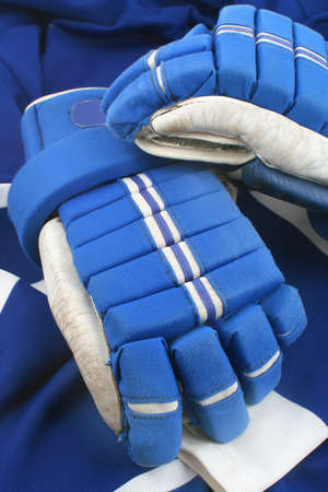 padding: professional protective hockey gloves protecting hands and fingers on top of a dark blue and white jersey