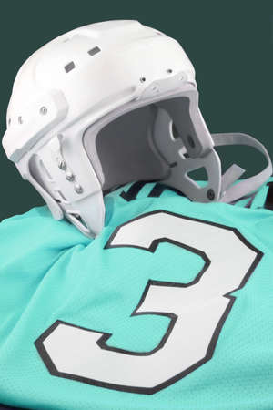 padding: professional protective hockey helmet for  protecting ones head, on teal blue  number 3 jersey Stock Photo