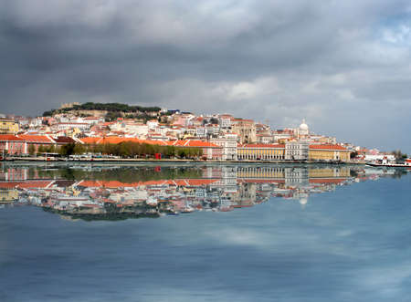 View of Lisbon from the other side of the river in Cacilhas with reflection  and stormy clouds