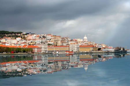 View of Lisbon from the other side of the river in Cacilhas with reflection  and stormy clouds and sun breaking through