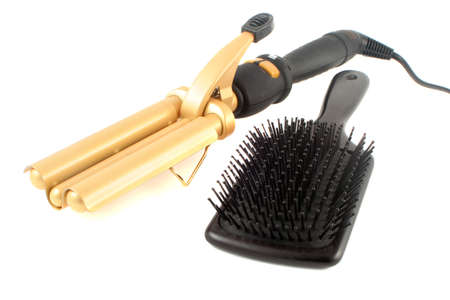 crimper: tripple barrel curling iron used on straight hair to make it wavy with black flat hairbrush ready for styling Stock Photo