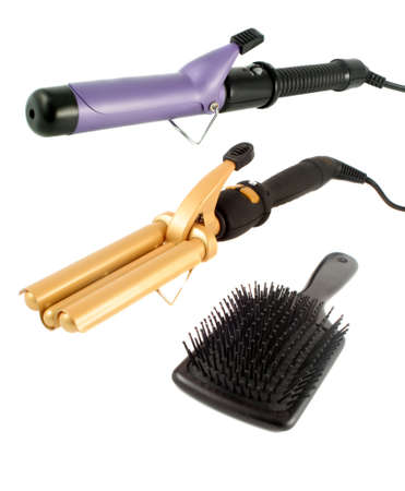 tripple: single and triple barrel curling irons used on straight hair to make it curly or wavy and flat hairbrush ready for hairstyling