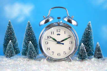 Conceptual image of wintertime with alarm clock,snow, and pine trees with blue sky