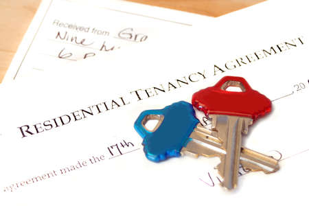 tenant: residential tenancy agreement document with blue and red keys on top and a rental cheque underneath