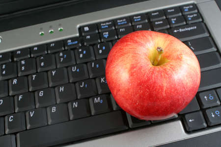 a business laptop with shiny red apple depicting workplace wellness or healthy school lunch Stock Photo