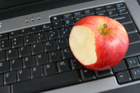 workplace wellness: a business laptop with shiny bitten red apple depicting workplace wellness or a healthy school snack