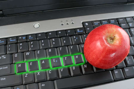 workplace wellness: the word health glowing on a laptop computer keyboard and shiny red apple beside  Stock Photo