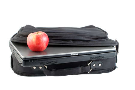 workplace wellness: laptop computer and healthy apple in carrying case for business on the move and workplace wellness Stock Photo