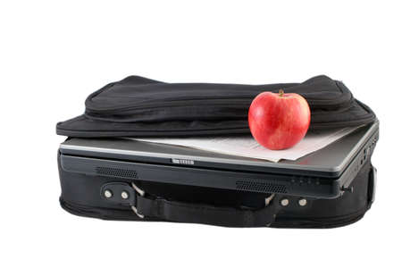 workplace wellness: laptop computer, papers and healthy apple in carrying case for business on the move and workplace wellness