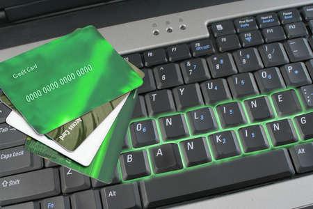 traslados: brillante de banca en l�nea en la computadora port�til con teclado verde de cr�dito y tarjetas de acceso