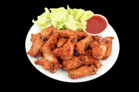 crispy chicken wings with hot and spicy barbecue dipping sauce and lettuce