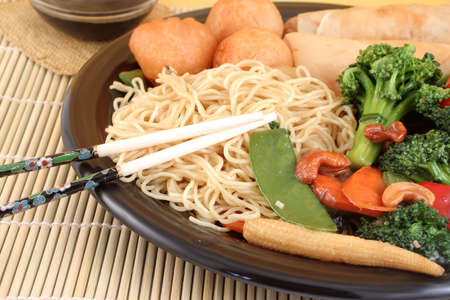 delicious chinese lo mein noodles and stir fry vegetables with cashews with chicken balls, spring rolls, soya  sauce and chopsticks on a bamboo placemat photo