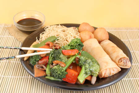 delicious chinese lo mein noodles and stir fry vegetables with cashews with chicken balls, spring rolls, soya  sauce and chopsticks on a bamboo placemat