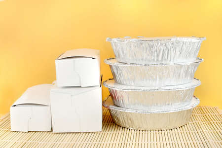 placemat: chinese food delivery or takeout aluminum covered containers and cardboard boxes on bamboo placemat  Stock Photo