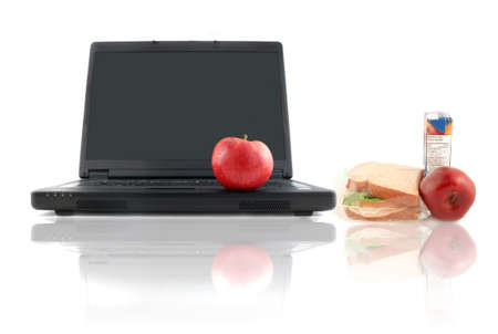 workplace wellness: a business laptop with shiny red apple and healthy sandwich lunch depicting workplace or school wellness
