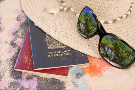 travel passports on beach towel and sand with hat and sunglasses showing a reflection of beautiful tropical palm trees  Stock Photo
