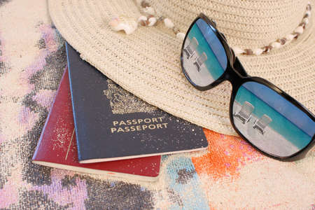 reflection: travel passports on beach towel and sand with hat and sunglasses reflecting beach chairs in a tropical paradise Stock Photo