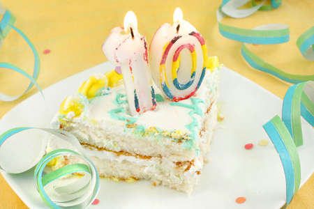 slice of tenth birthday cake with lit candle, confetti, and ribbon (shallow depth of field) Stock Photo