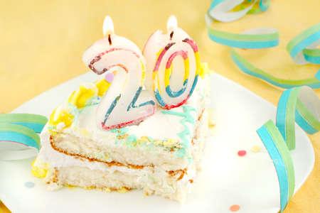 twentieth: slice of twentieth birthday cake with lit candle, confetti, and ribbon (shallow depth of field)