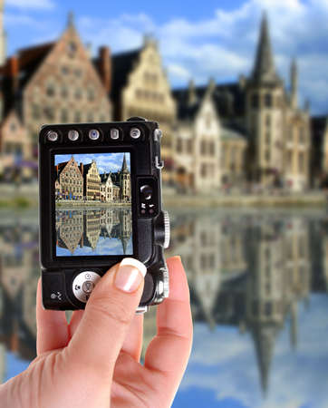 gabled: taking a picture of gabled houses along a canal  in Gent,  Belgium with reflection on the water