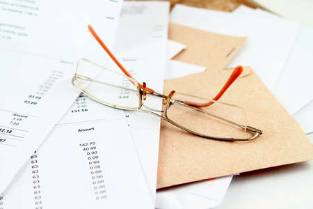 Different bills to be paid and envelopes with eyeglasses on top for prompt payments photo
