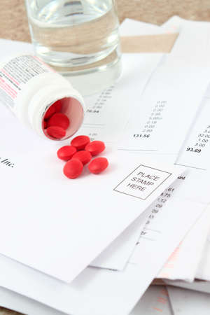 Different bills to be paid and envelopes with red pills and water to soothe the headache of paying bills