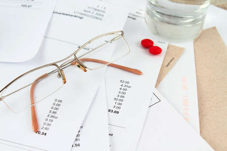 Different bills to be paid. envelopes and eyeglasses with red pills, and water to soothe the headache of paying bills photo