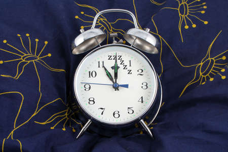 12 oclock: alarm clock resting on a pillow showing 11 oclock, time to go to bed with zzzzz as 12 oclock