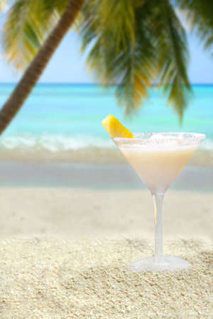a tropical pina colada drink with pineapple in a sand mound on a tropical beach with palm tree and ocean in the background