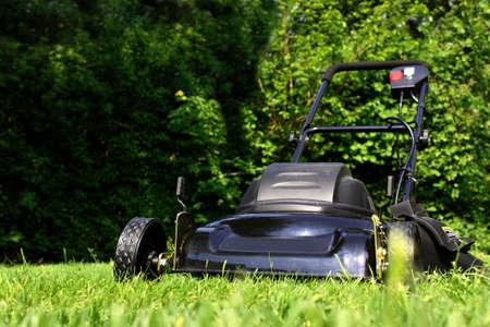 Zwarte grasmaaier klaar te snijden werf gras (korte scherptediepte)