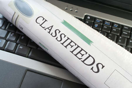 classifieds: Classified ads section of the newspaper  laying on a laptop Stock Photo