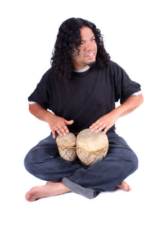 percussionist: Funky long haired ethnic African American and Native Indian male playing bongo drums on a white background