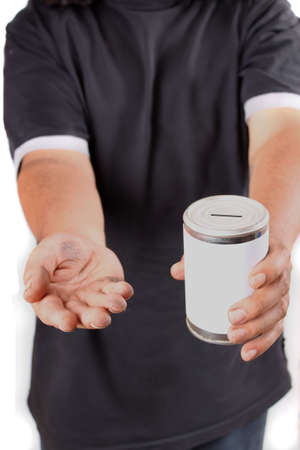Homeless man with dirty hands holds a tin can asking for change