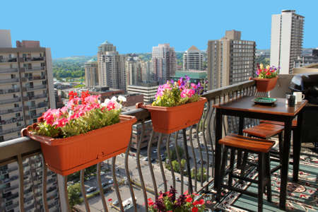 Rooftop patio with table and stool chairs, colorful flower baskets along a balcony railing with Calgary building skyline in the background Stock Photo