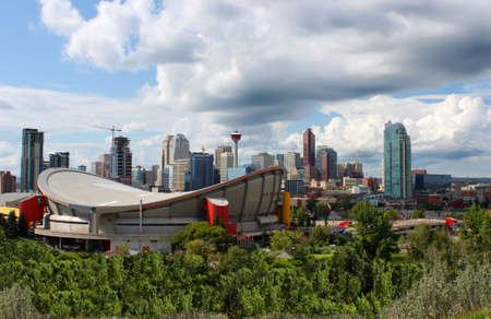 Skyline view of highrise office and apartment buildings in Calgary, Alberta, Canada with the Saddledome in the foreground and dramatic sky photo