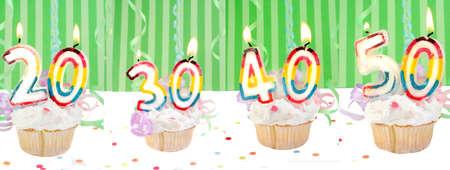 기념 생일 컵케익 조명 된 촛불와 20, 30, 40, 50 같은 색종이와 녹색 줄무늬 배경