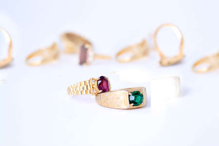 different colored stone rings with gold bands in a white background focus on purple ring