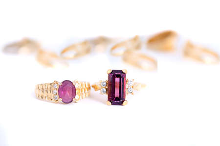 heirlooms: different purple stone rings with gold bands in a white background