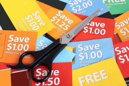 thrifty: Cutting coupons in different colors, and price ranges from free to a few dollars (short depth of field)
