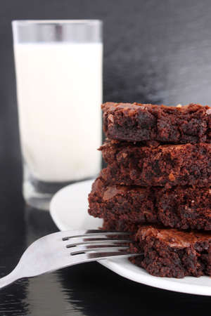 chocolaty: Chocolate fudge brownies on black with glass of milk in the background and a fork on the plate Stock Photo