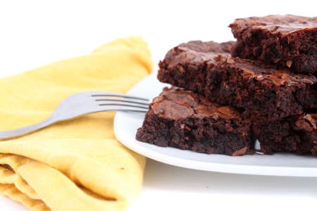 chocolaty: Pile of chocolate fudge brownies on a plate with a white  background (short depth of field)