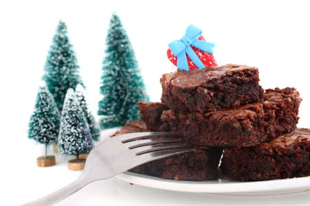 chocolaty: Pile of christmas chocolate fudge brownies on a plate with a white  background (short depth of field)