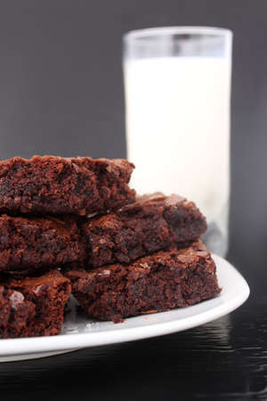 brownies: Pile of chocolate fudge brownies on a plate with a glass of milk in the  background (short depth of field)